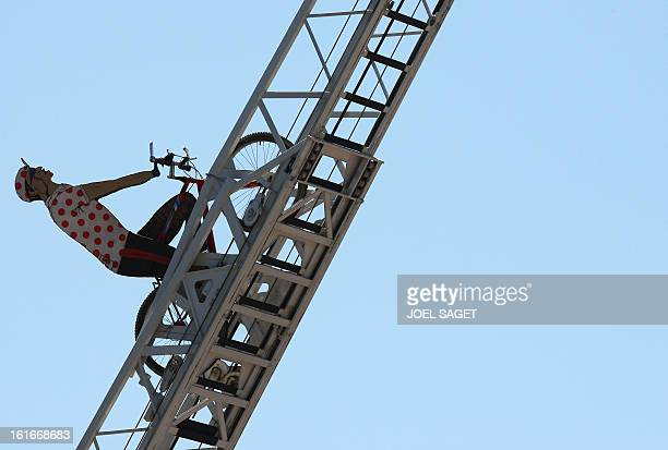 A model wearing a redandwhite polka dotted jersey is displayed on a firefighter ladder in SemurenAuxois before the sixth stage of the 94th Tour de...