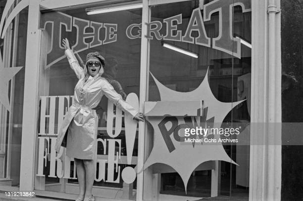 Model wearing a silver raincoat and sunglasses, her arms outstretched, stands in front of a shop window, on which is a comic-style 'pow!', in London,...