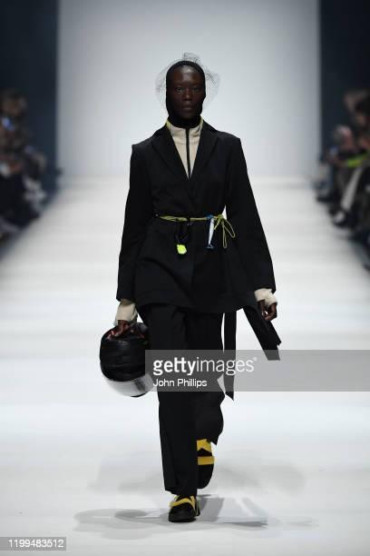 Model wearing a suit by Lara Krude, shirt by Hessnatur, hood by Falke, hairnet by Spatz Hutdesign, leg pieces by Trippen, socks by Swedish Stockings...
