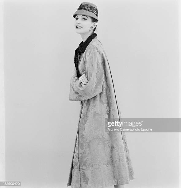 Model wearing a three-quarter length coat and feathered hat by Chinotto, Turin, circa 1955.
