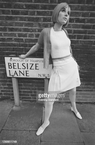 Model wearing a twin set and skirt with pleats on Belsize Lane in London, UK, 13th February 1967.