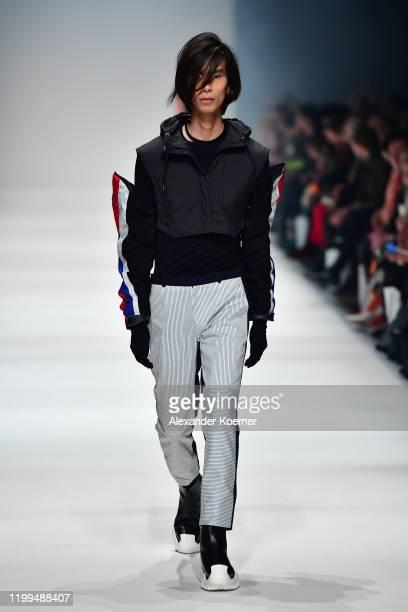 Model wearing a vest by Arys, necklaces by Layla De Mue, sleeves by Vintage, top by Falke, trousers by Schmidttakahashi, gloves by Falke, shoes by...