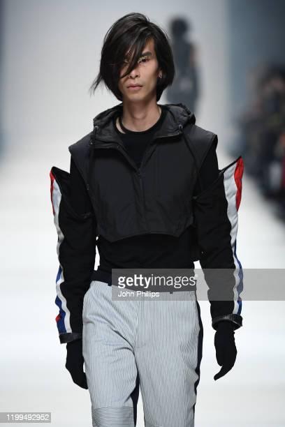 Model wearing a vest by Arys, necklaces by Layla De Mue, sleeves by Vintage, top by Falke, trousers by Schmidttakahashi and gloves by Falke walks the...