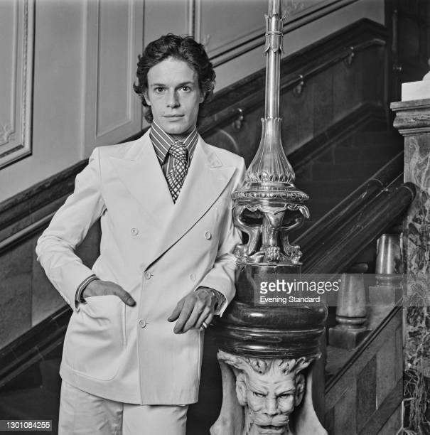 Model wearing a white cotton suit with a shirt and tie, UK, 30th May 1973.