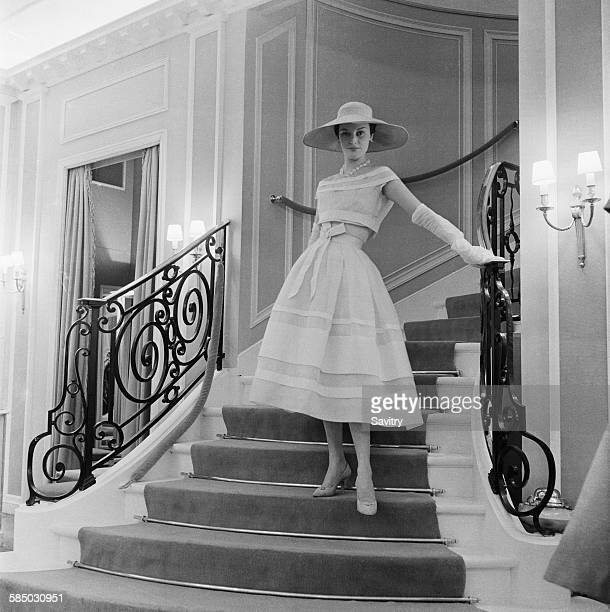 Model wearing a white organdie dress by Dior, Paris, March 1956. The dress is bound with white grosgrain ribbons, showing the high Empire bosom and...
