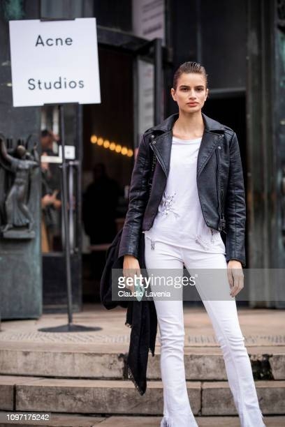Model, wearing a white t-shirt, white jeans and black leather jacket, is seen in the streets of Paris after the Acne Femme show on January 20, 2019...
