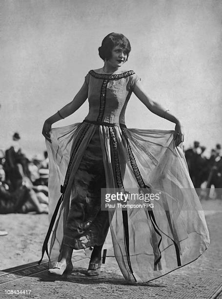 A model wearing a yellow organdie over gold evening gown during a fashion show held at Biltmore Beach in Rye New York circa 1920