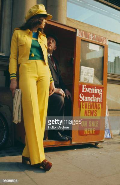 A model wearing a yellow trouser suit and cap buys a copy of the 'Evening Standard' circa 1975