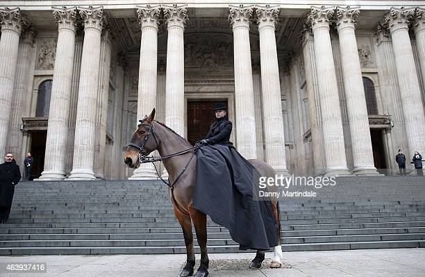 A model wearing an dress designed by Sarah Burton for Alexander McQueen sits on a horse outside a memorial service for Professor Louise Wilson during...