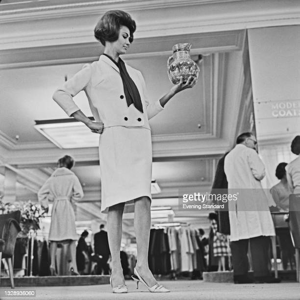 Model wearing an elegant skirt suit with a dark-coloured scarf, UK, 13th September 1965.