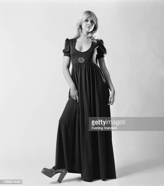 Model wearing an Empire-line dress with short sleeves, and platform shoes, UK, November 1971.