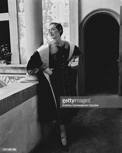A model wearing an evening dress and coat and a veillike mask Italy 21st July 1951