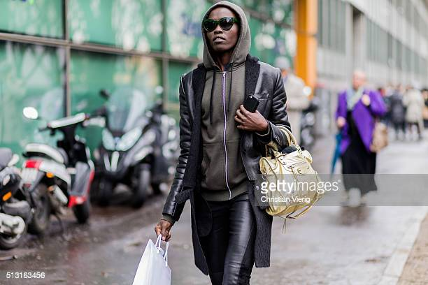 A model wearing an olive hoody a golden bag and a leahter coat and pants seen outside Giorgio Armani during Milan Fashion Week Fall/Winter 2016/17 on...