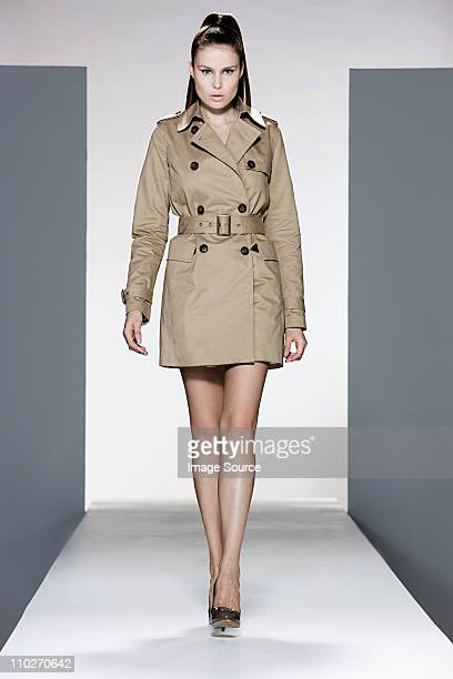 model wearing beige raincoat on catwalk at fashion show - vertical stock pictures, royalty-free photos & images
