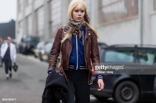 A model wearing black striped pants brown leather jacket zip jacket outside Baum Pferdgarten at the Copenhagen Fashion Week Autumn/Winter 17 on...