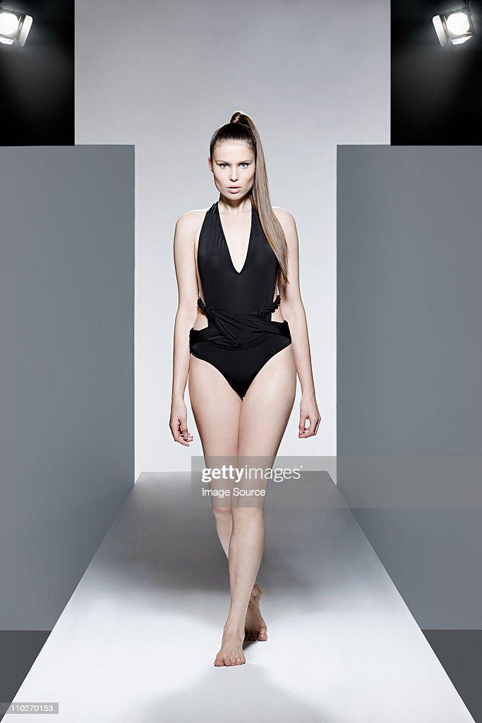 Model wearing black swimsuit on catwalk at fashion show : Stock Photo