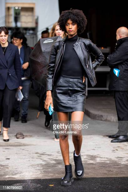 Model, wearing black top, black leather mini skirt, black leather jacket and black boots, is seen outside the Chanel show during Paris Fashion Week -...
