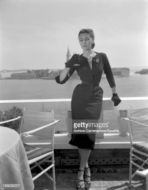 Model wearing Christian Dior fashions near the Piazza San Marco in Venice, 3rd June 1951. The island of San Giorgio Maggiore is visible in the...