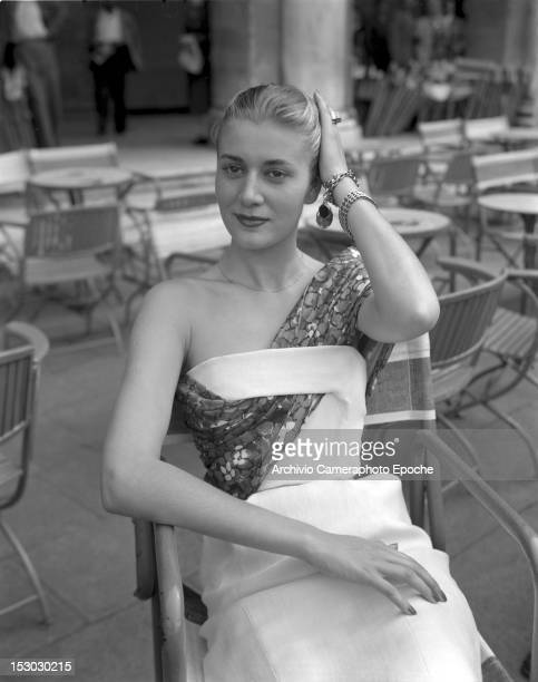 A model wearing Christian Dior fashions on the Piazza San Marco in Venice sitting on a cafè chair 3rd June 1951