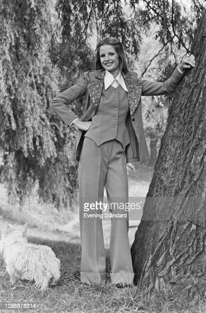 Model wearing creased wide leg trousers and a waistcoat and jacket, UK, October 1971.