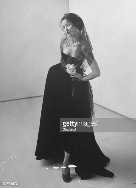 Model wearing evening dress with veil as part of 'new look' postwar by designer Edith Head