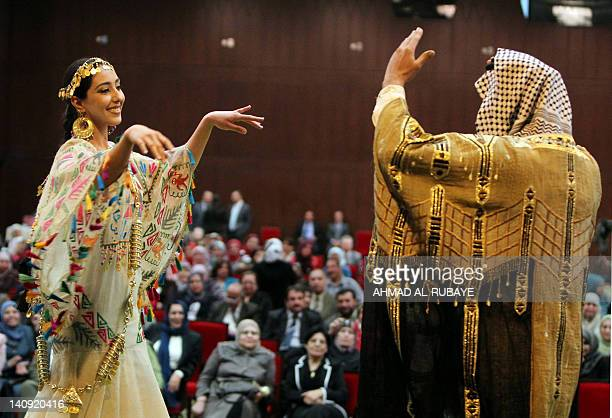 A model wearing fashion from Iraqi folklore dances with a man in traditional clothing during celebrations in Baghdad for International Women's Day...