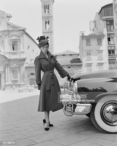 A model wearing Italian fashions in front of a car marked 'US Consulate Florence' 21st July 1951