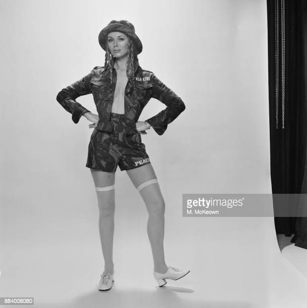 A model wearing khaki camouflage short jacket high waisted shorts nude parisienne tights and white oxford midheels shoes UK 3rd May 1971