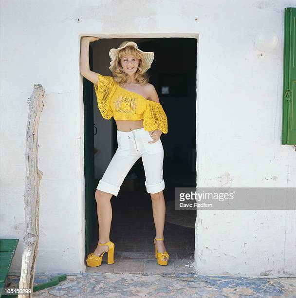 A model wearing kneelength trousers and a yellow blouse circa 1978