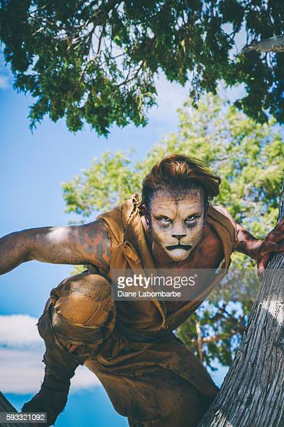model wearing lion makeup & costume  leaping from a tree - lion feline stock photos and pictures