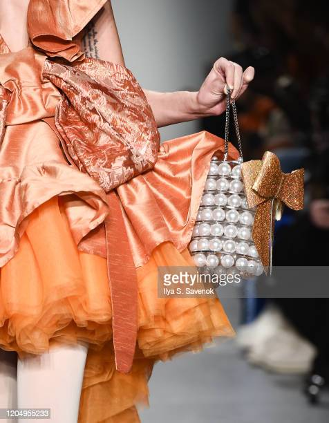 A model wearing Monalizabeth with hats by 20Summerslove accessories by SSY Designs and hair accessory by Katie Lares walks the runway during the...