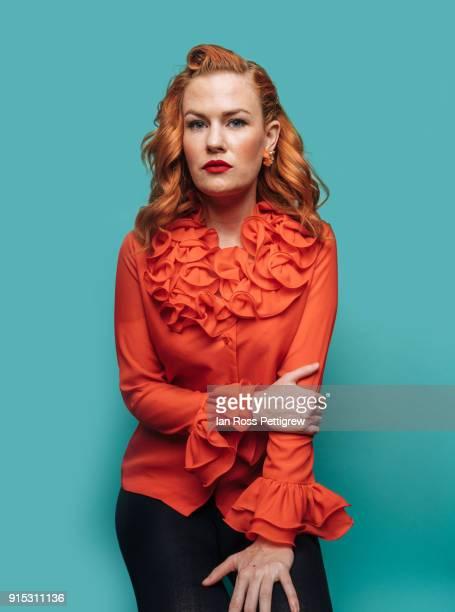 Model wearing orange shirt on blue background