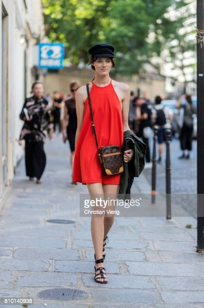 A model wearing red dress flat cap Louis Vuitton bag outside Valentino during Paris Fashion Week Haute Couture Fall/Winter 20172018 Day Four on July...
