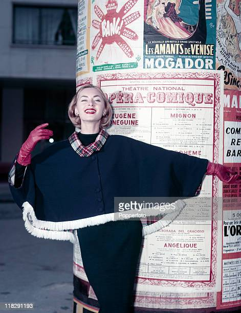 A model wearing red gloves and a black dress with a black cape trimmed in tartan in front of a poster kiosk in Paris circa 1960