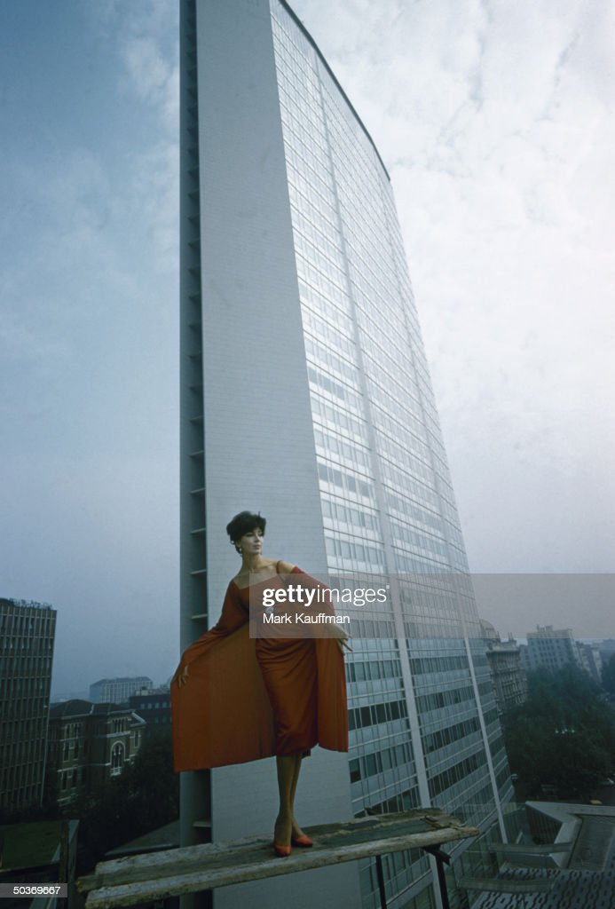 Model wearing red panelled cocktail dress by Italian designer Fabiani posing against backdrop of the Pirelli building, skyscraper designed by Gio Ponti.