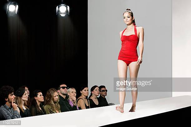 model wearing red swimsuit on catwalk at fashion show - modeshow stockfoto's en -beelden