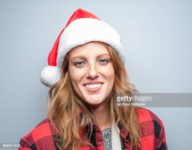 Model wearing santa hat and plaid jacket