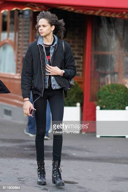 A model wears a balck bomber jacket a blue denim jacket black pants black boots holds a smartphone outside Proenza Schouler during Paris Fashion Week...