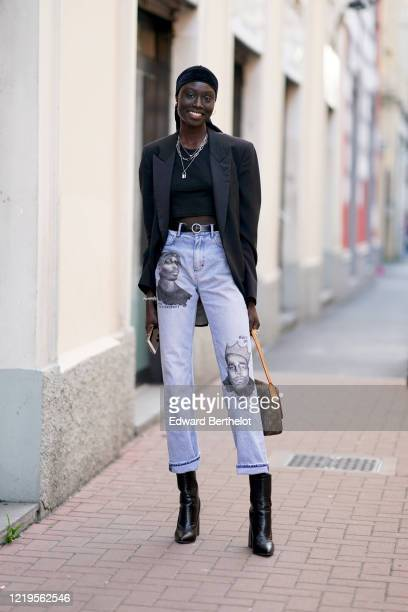 A model wears a bandanna a necklace a black oversized blazer jacket a cropped top a leather belt blue jeans with cuffs and printed faces a Vuitton...