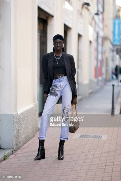 Model wears a bandanna, a necklace, a black oversized blazer jacket, a cropped top, a leather belt, blue jeans with cuffs and printed faces, a...