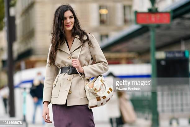 Model wears a beige double breasted jacket, a large belt, a bag, a purple lustrous silky flowing dress, outside Louis Vuitton, during Paris Fashion...