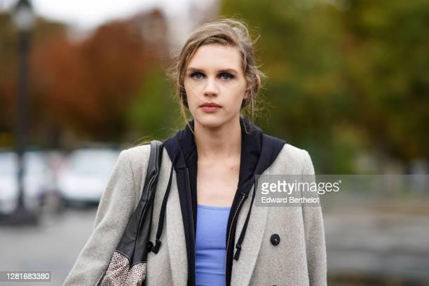 Model wears a beige long coat, blue/mauve cropped top, a black hoodie sweater, a bag, outside Chanel , during Paris Fashion Week - Womenswear Spring...