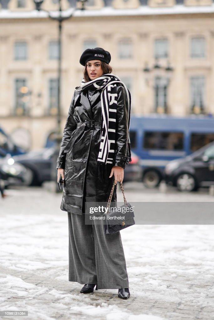 e7e773f6b A model wears a beret, a black shiny pvc trench coat, a black and ...