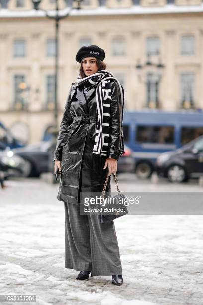 A model wears a beret a black shiny pvc trench coat a black and white scarf a Chanel bag flare pants outside Alexis Mabille during Paris Fashion Week...