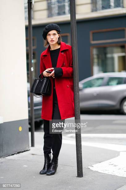 A model wears a beret hat a red coat black pants black shoes outside APC during Paris Fashion Week Womenswear Fall/Winter 2018/2019 on March 5 2018...