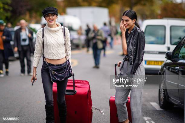 A model wears a beret hat a white bare belly turtleneck wool pull over black jeans and carries red luggage a model wears a black leather jacket a bag...