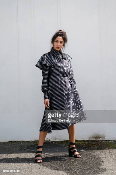 A model wears a black and silver shiny dress in the form of a trench coat during Feeric Fashion Week 2018 on July 22 2018 in Sibiu Romania