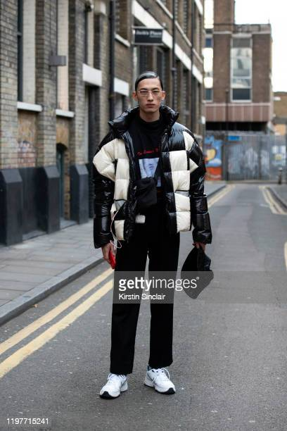 A model wears a black and white puffer jacket with black trousers and Nike trainers during London Fashion Week Men's January 2020 on January 04 2020...