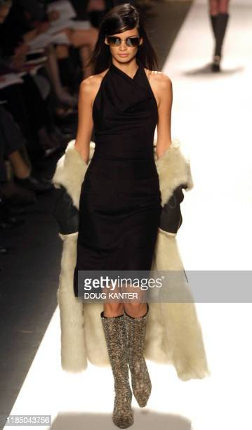 A model wears a black and white shearling black cashmere halter dress sunglasses and feather beaded boots at the Oscar de la Renta show during Fall...