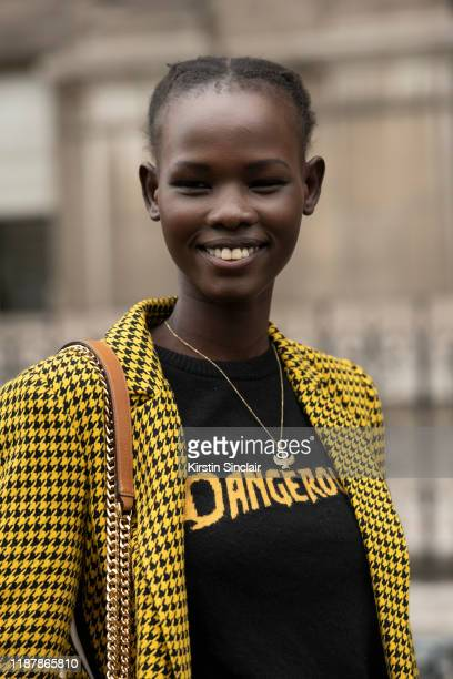 A model wears a black and yellow houndstooth jacket on September 26 2019 in Paris France